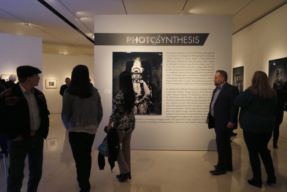 Photo -  Guests look at photographs in Will Wilson's Photo/synthesis exhibition of tintypes of American Indians at the Fred Jones Jr. Museum of Art. The exhibition was funded through a grant from the National Endowment for the Arts. Some in Oklahoma's arts community worry about the fate of that agency under the Trump administration. Photo by Sarah Phipps, The Oklahoman