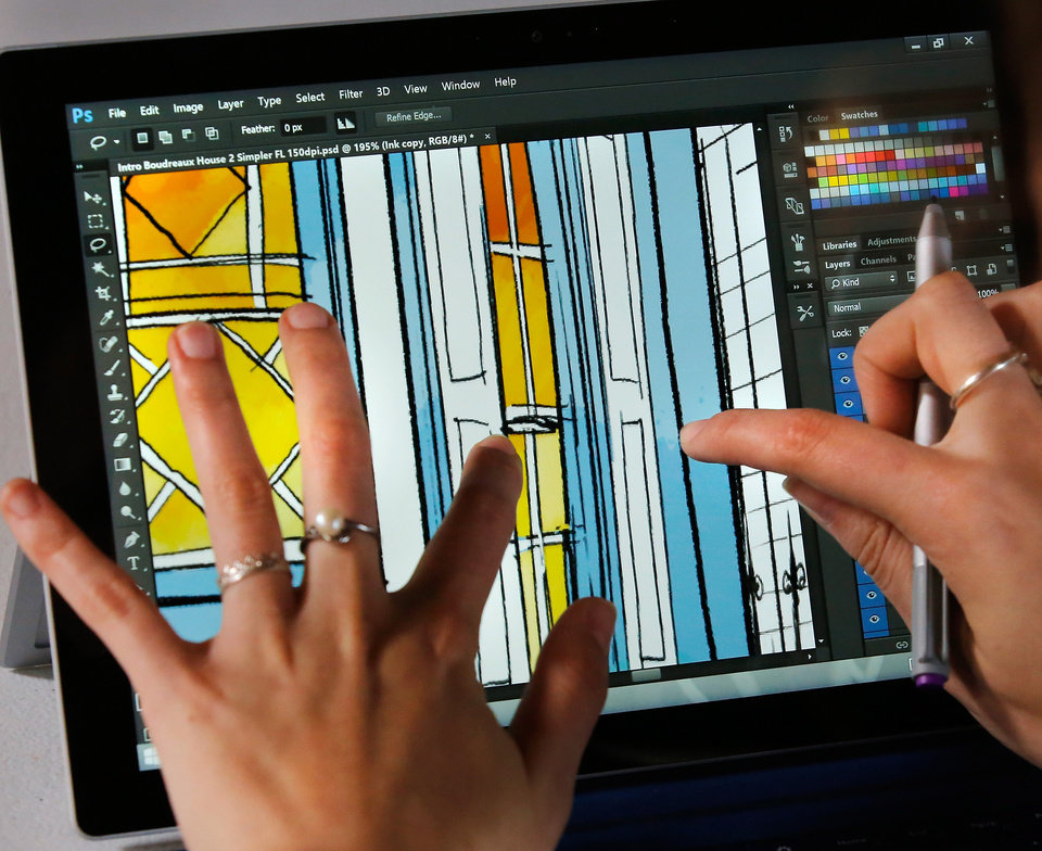 Photo -  Sarah Lauffenburger zooms in on the detail in the artwork on her laptop. [Photo by Jim Beckel, The Oklahoman]