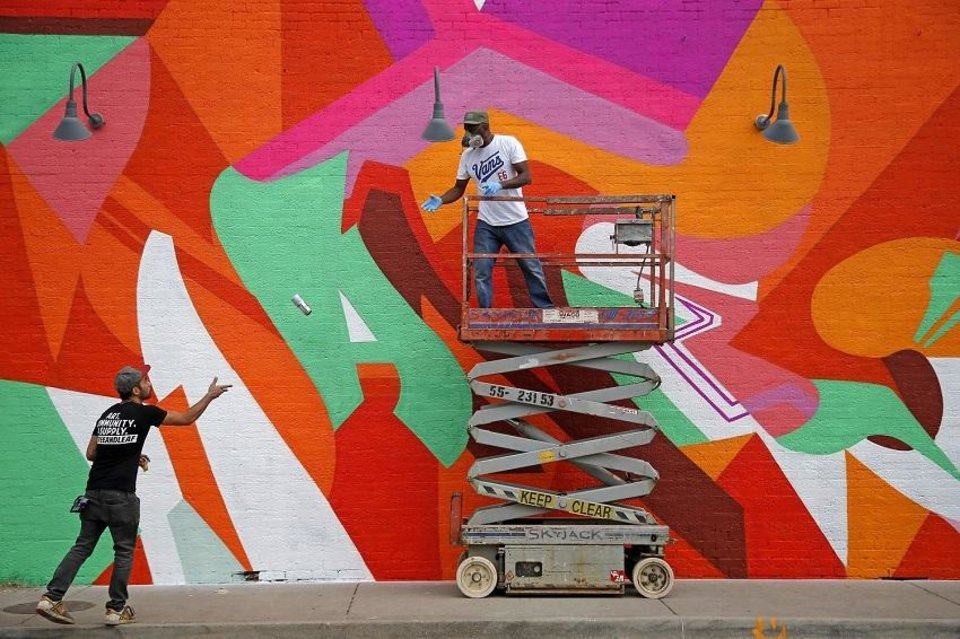 Photo - Artist Chris Foxworth of Kansas City, left, tosses a can of paint to artist Wane Peterkin as he paints the side of a building during the Plaza Walls Mural Expo, which takes place in conjunction with the Plaza District Festival, in Oklahoma City, Saturday, Sept. 30, 2017. [Bryan Terry/The Oklahoman Archives]