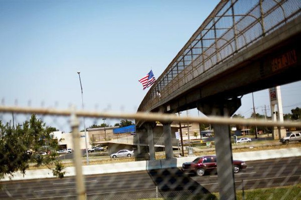 Photo - Standing on a pedestrian bridge, Ted Krey, of Yukon, holds an American Flag over I-240 on Wednesday, Aug. 24, 2011. Krey says he will hold the flag over traffic from a different pedestrian bridge around Oklahoma City everyday until Sept. 11. Photo by John Clanton, The Oklahoman ORG XMIT: KOD