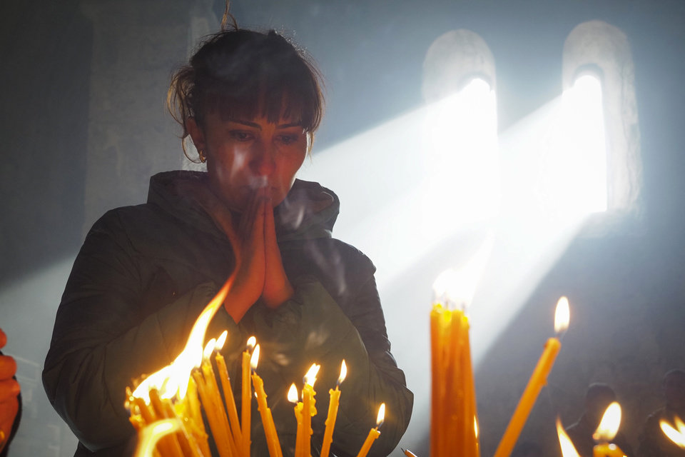 Photo -  A woman lights candles inside a church of the Dadivank, an Armenian Apostolic Church monastery dating to the 9th century, as ethnic Armenians leave the separatist region of Nagorno-Karabakh to Armenia, Saturday, Nov. 14, 2020. The territory is to be turned over to Azerbaijan on Sunday as part of territorial concessions in an agreement to end six weeks of intense fighting with Armenian forces. Hundreds of thousands of Azeris were displaced by the war that ended in 1994. It is unclear when any civilians might try to settle in Karvachar — which will now be known by its Azeri name Kalbajar — or elsewhere. (AP Photo/Dmitry Lovetsky)
