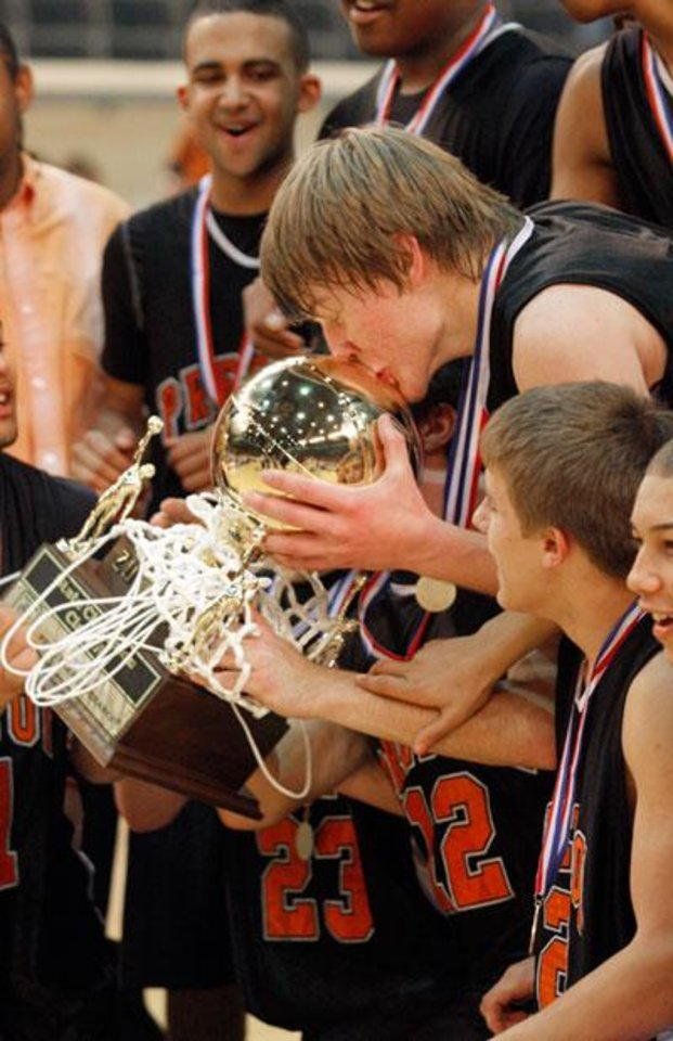 Photo -  Preston's John Paul Yeager kiss the champion trophy following the boys Class A State Basketball finals between Preston and Texhoma, Saturday, March 7, 2009, at the State Fair Arena in Oklahoma City . PHOTO BY BRENDA O'BRIAN, THE OKLAHOMAN