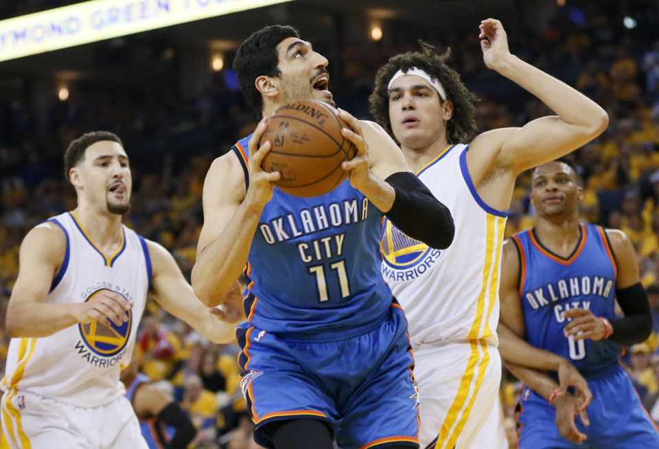 Photo - Oklahoma City's Enes Kanter (11) tries to get past Golden State's Anderson Varejao (18) as Klay Thompson (11) watches during Game 5 of the Western Conference finals in the NBA playoffs between the Oklahoma City Thunder and the Golden State Warriors at Oracle Arena in Oakland, Calif., Thursday, May 26, 2016. Photo by Nate Billings, The Oklahoman