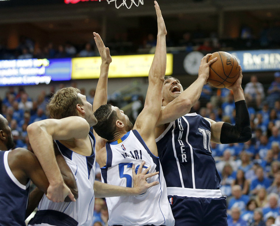 Photo - Oklahoma City's Enes Kanter (11) goes to the basket beside Dallas' Salah Mejri (50) and Dirk Nowitzki (41) during Game 3 of the first round series between the Oklahoma City Thunder and the Dallas Mavericks in the NBA playoffs at American Airlines Center in Dallas, Thursday, April 21, 2016. The Thunder won 131-102. Photo by Bryan Terry, The Oklahoman