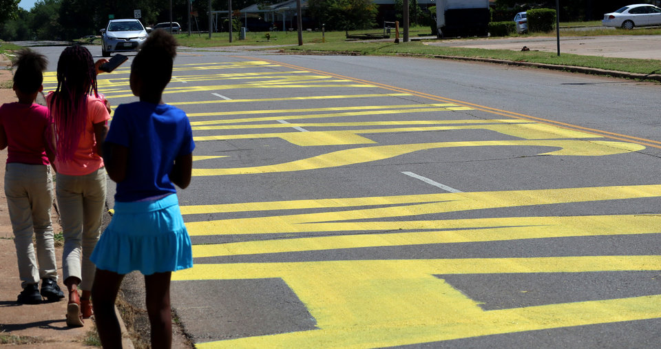 Photo - Young girls take video of the Black Lives Matter! that was painted on the west bound lanes of Springlake Dr., just east of the intersection of NE 36th and Kelley Ave.,Wednesday, June 24, 2020. [Doug Hoke/The Oklahoman]