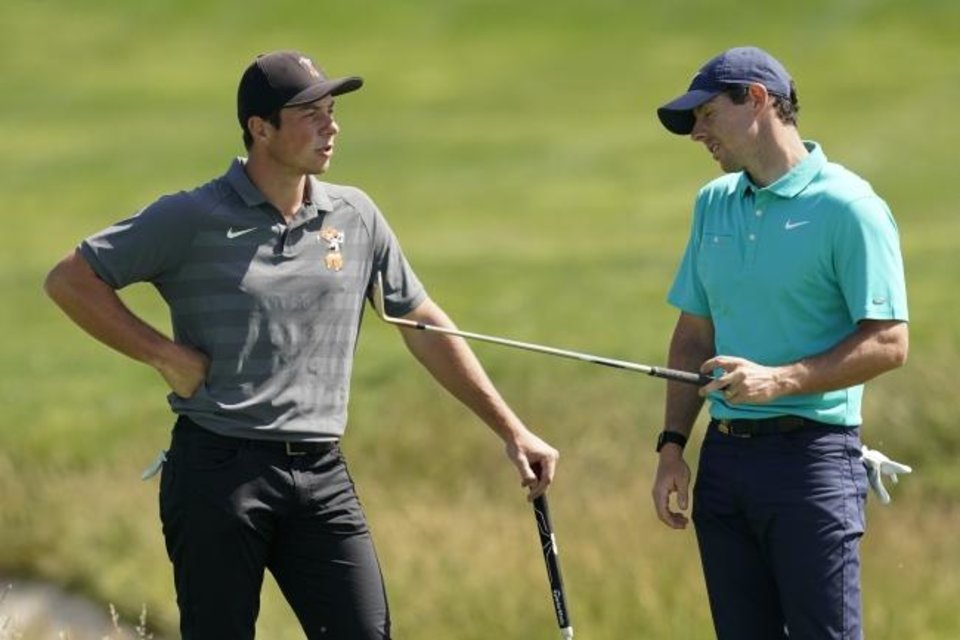 Photo -  Former Oklahoma State star Viktor Hovland, left, and Rory McIlroy talk on the 17th hole during a practice round Tuesday for the U.S. Open in Pebble Beach, Calif. [AP Photo/David J. Phillip]