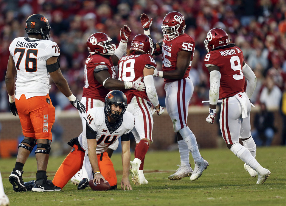 Photo - Oklahoma State's Taylor Cornelius (14) gets up slowly near Dylan Galloway (76) after being tackled for a loss as Oklahoma's Neville Gallimore (90), Curtis Bolton (18), Kenneth Mann (55) and Kenneth Murray (9) celebrate in the third quarter of a Bedlam college football game between the University of Oklahoma Sooners (OU) and the Oklahoma State University Cowboys (OSU) at Gaylord Family-Oklahoma Memorial Stadium in Norman, Okla., Nov. 10, 2018. OU won 48-47. Photo by Nate Billings, The Oklahoman