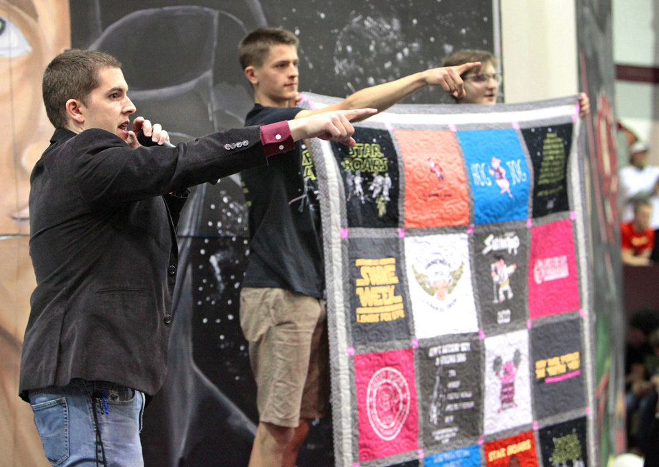 Photo - Edmond Memorial High School teacher Josh DeLozier, left, auctioned off a quilt during the final assembly for Swine Week. The quilt sold for $5,000. Photo By David McDaniel, The Oklahoman