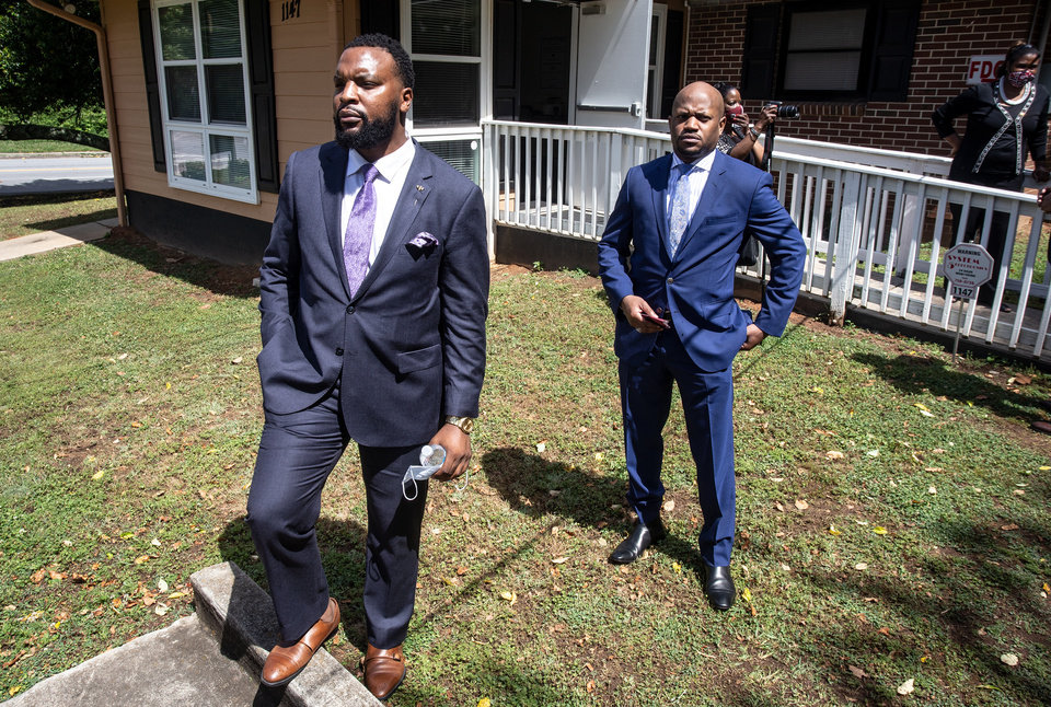 Photo -  Lee Merritt, left, and Chris Stewart, attorneys for the mother of Ahmaud Arbery, are seen at a news conference on Wednesday, May 19, 2020, in East Point, Georgia. The attorneys appeared and spoke at a news conference held by the Atlanta branch of the NAACP. After a video of the shooting of Arbery emerged on social media, the Georgia Bureau of Investigation, arrested Gregory McMichael, 64, and his son, Travis McMichael, 34, and they were jailed on murder and aggravated assault charges. (AP Photo/Ron Harris)