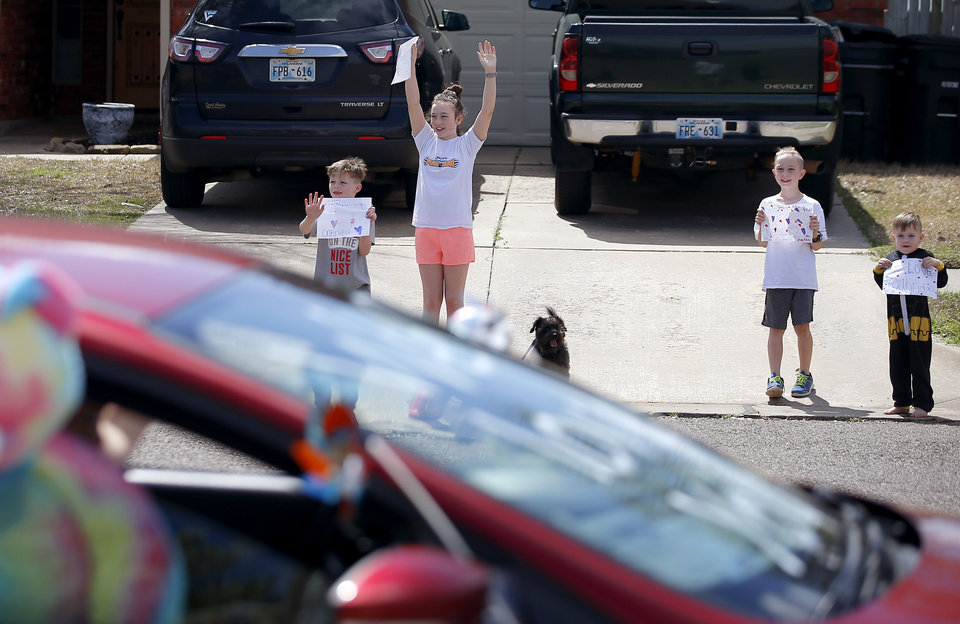 Photo - Oakridge Elementary students first -grader Isaac Madden 6, left,  fifth-grader Emma Madden, 11, third-grader Evan Madden, 8, along with their three-year-old brother Hudson Madden hold signs as an Oakridge Elementary faculty caravan drives through their neighborhood around the Moore school, Tuesday, March 24, 2020. [Bryan Terry/The Oklahoman]