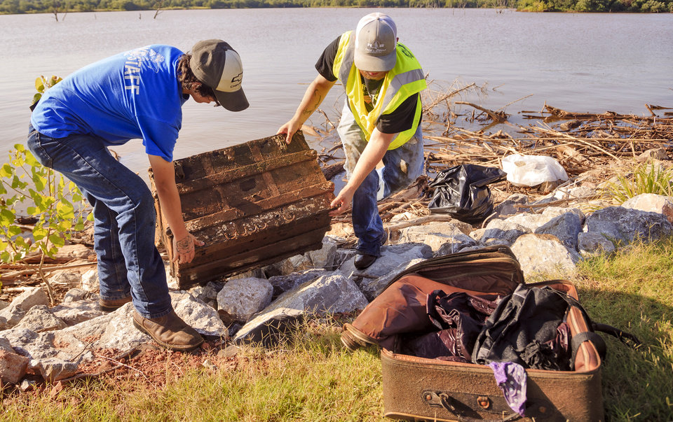 Photo -  Arcadia Lake maintenance workers Matthew Delk, left, and Brandon Story pull a wooden chest and suitcase full of clothes from the water at Carl Reherman Park on Tuesday. [Photo by Chris Landsberger, The Oklahoman]