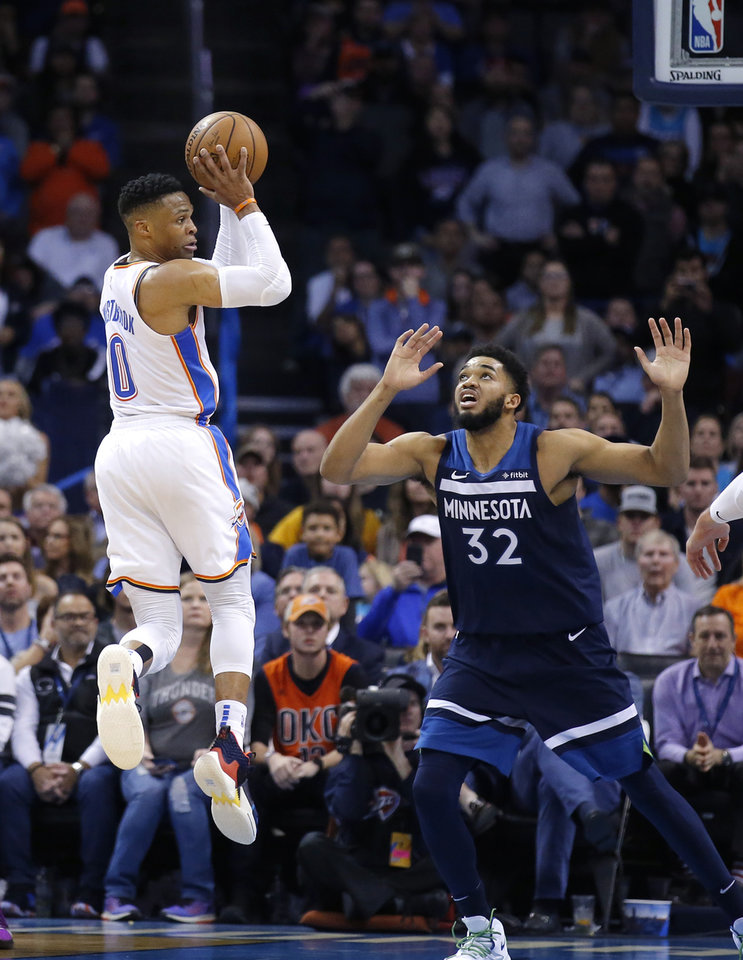 Photo - Oklahoma City's Russell Westbrook (0) passes the ball as Minnesota's Karl-Anthony Towns (32) defends during the NBA game between the Oklahoma City Thunder and Minnesota Timberwolves at the Chesapeake Energy Arena, Tuesday, Jan. 8, 2019. Photo by Sarah Phipps, The Oklahoman