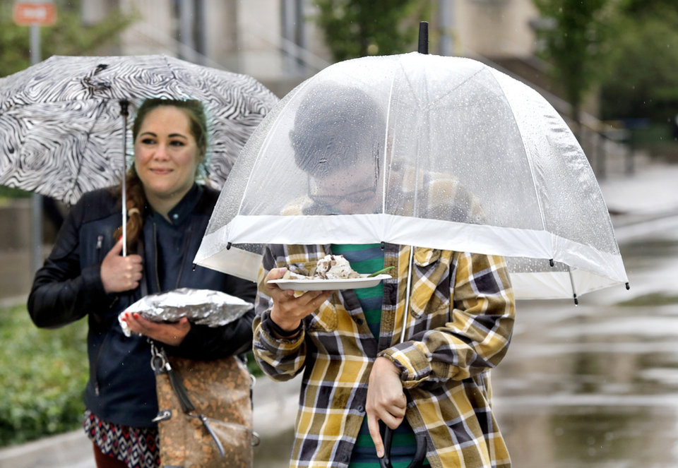 Photo - Two people keep themselves and their meals dry after purchasing food during the lunch hour on the opening day of the festival. The Festival of the Arts is a showplace for the visual, performing and culinary arts, bringing a variety of talented artists together in Bicentennial Park in Oklahoma City.  The annual festival has been an OKC tradition since 1967, and is a signature event for the Arts Council, with an average of 750,000 Festival attendees. The festival continues every day this week from 11 a.m. to 9 p.m. and ends at 6 o'clock Sunday evening, April 28, 2019.   Photo by Jim Beckel, The Oklahoman.