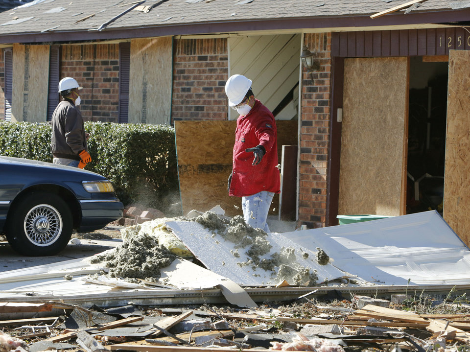 Photo -  A restoration crew removes debris Monday from a home at 12501 Whispering Hollow Drive in Oklahoma City.
