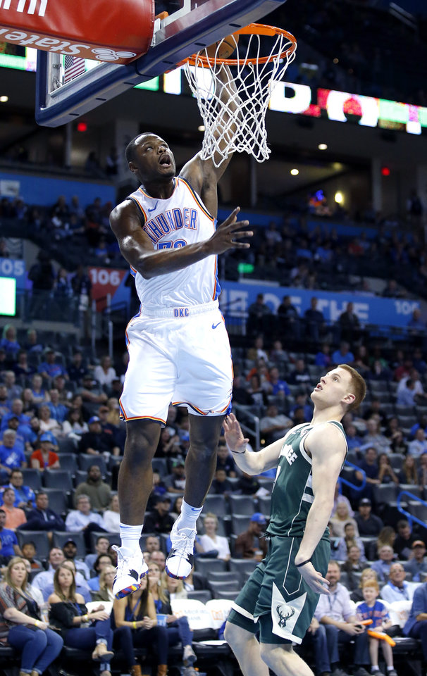 Photo - Oklahoma City's Deonte Burton (30) dunks in front of Milwaukee's Donte DiVincenzo (9)  during a NBA preseason game between the Oklahoma City Thunder and Milwaukee Bucks at Chesapeake Energy Arena in Oklahoma City,  Tuesday, Oct. 9, 2018. Photo by Sarah Phipps, The Oklahoman