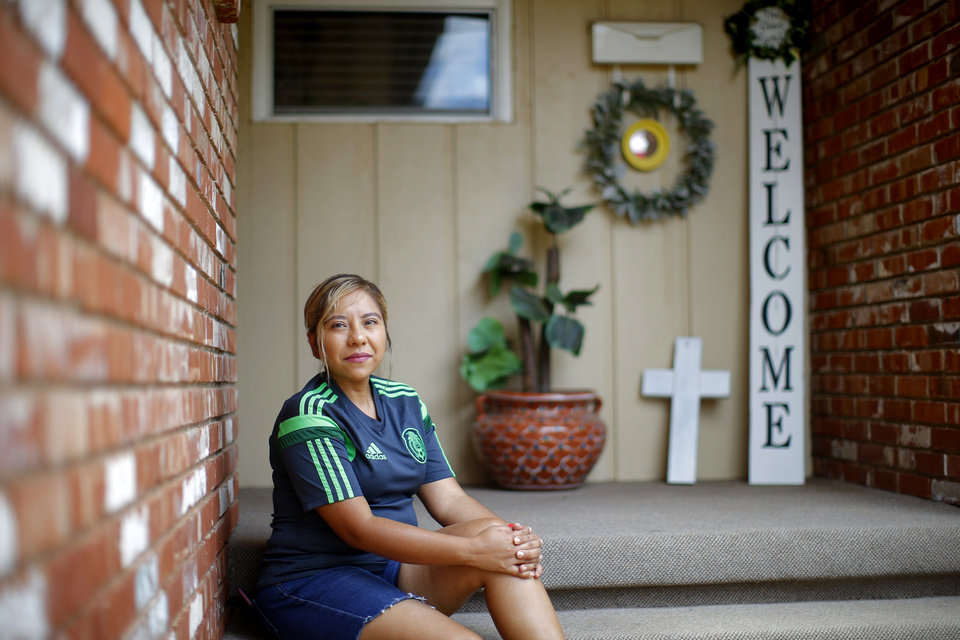 Photo -  Jess Olivo, who was diagnosed with COVID-19 and has recovered, sits on the steps outside her Warr Acres area home on Friday. Five other members of Olivo's family contracted COVID-19 amid a surge of cases among Oklahoma City's Latino community. [Bryan Terry/The Oklahoman]