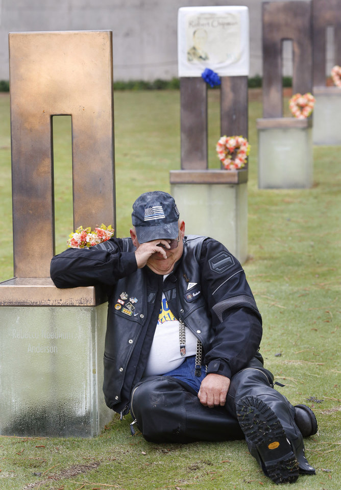 Photo -  Overcome with emotion as he sits by the chair with the name of Rebecca Needham Anderson on it, Brad Black weeps. Black said he was at the bombing site for nearly three weeks after the attack, volunteering with the Red Cross. He said he developed a personal admiration for Anderson because she, too, was a volunteer, who rushed to the site as soon as she heard of the bombing. [Photo by Jim Beckel, The Oklahoman]