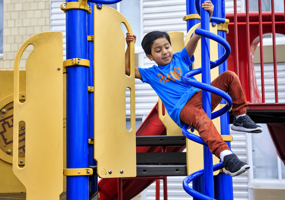 Photo -  A child of a client at the City Rescue Mission plays on the shelter's playground Monday afternoon. Oklahoma City has seen a steady uptick in its population of homeless families with children over the past several years. [Photo by Chris Landsberger, The Oklahoman]