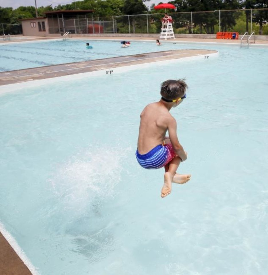 Photo -  Camdyn Hubbard, 7, jumps into the water Saturday at Will Rogers Family Aquatic Center.