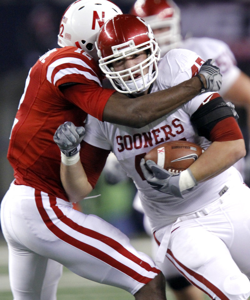 Photo - Nebraska's Courtney Osborne (12) tries to bring down Oklahoma's Trent Ratterree (47) during the Big 12 football championship game between the University of Oklahoma Sooners (OU) and the University of Nebraska Cornhuskers (NU) at Cowboys Stadium on Saturday, Dec. 4, 2010, in Arlington, Texas.  Photo by Chris Landsberger, The Oklahoman