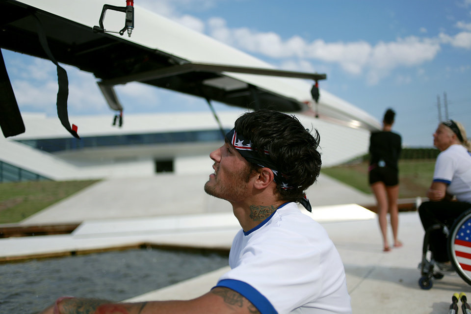 Photo - Tony Davis rests with rowing partner Jacqui Kapinowski (background at right) rest while coaches return their boat to the Devon Boathouse following practice on the Oklahoma River in Oklahoma City on Tuesday, June 14, 2011. Photo by John Clanton, The Oklahoman