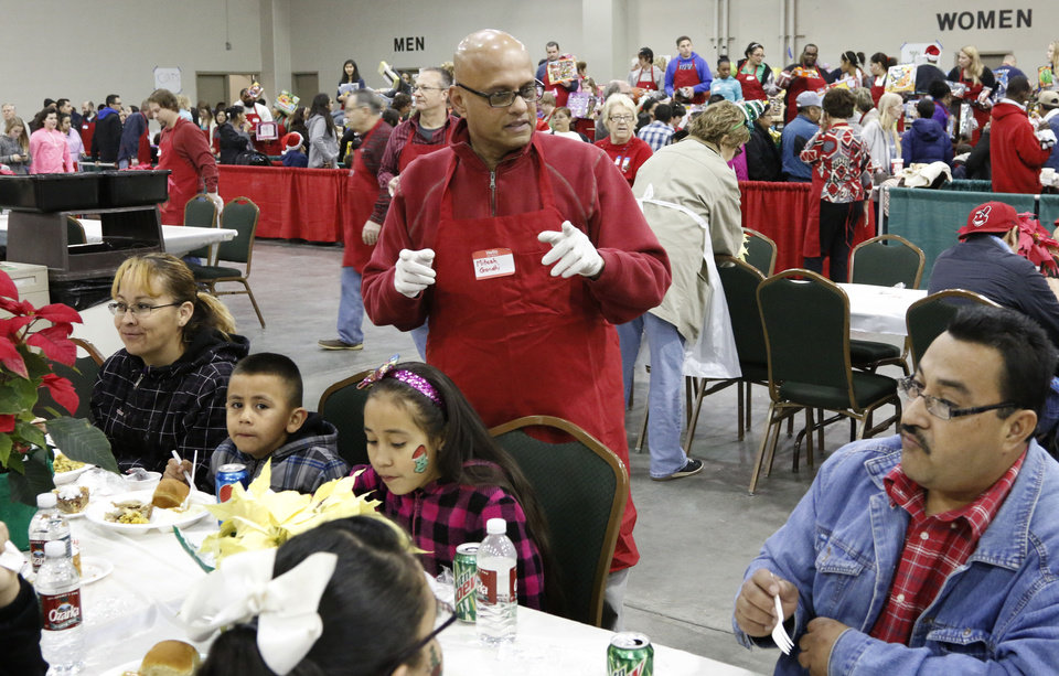 Photo -  Volunteer Mitesh Gandhi takes requests during the annual Red Andrews Christmas dinner last year at the Cox Convention Center in Oklahoma City. [Photo by Paul Hellstern, The Oklahoman Archives]