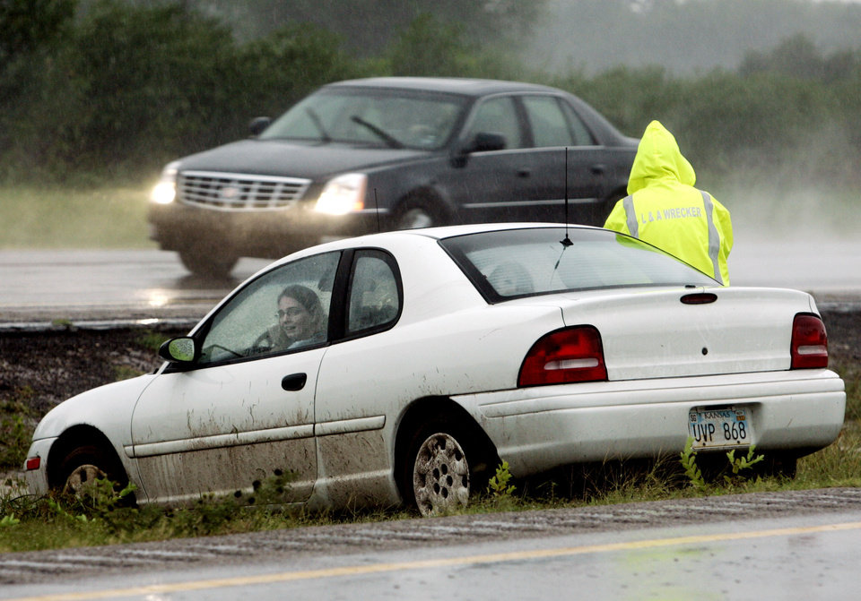 Photo - A wrecker driver stands beside a motorist stranded in the I35 median north of Purcell, Oklahoma on Sunday morning, August 19, 2007.  BY STEVE SISNEY, THE OKLAHOMAN