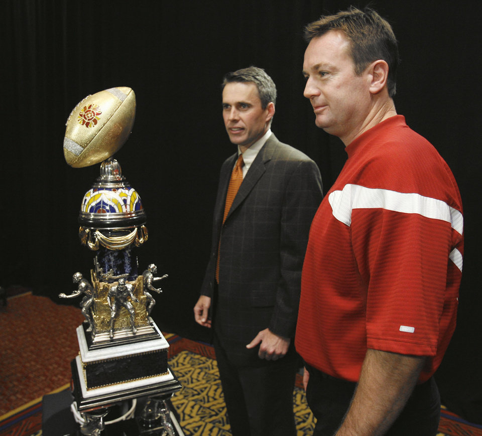 Photo - Boise State head coach Chris Petersen and University of Oklahoma (OU) college football head coach Bob Stoops pose with the Tostitos Fiesta Bowl Trophy at the Camelback Inn Fiesta Bowl media hotel in Phoenix, Arizona on Sunday, December 31, 2006.  by Steve Sisney/The Oklahoman ORG XMIT: KOD