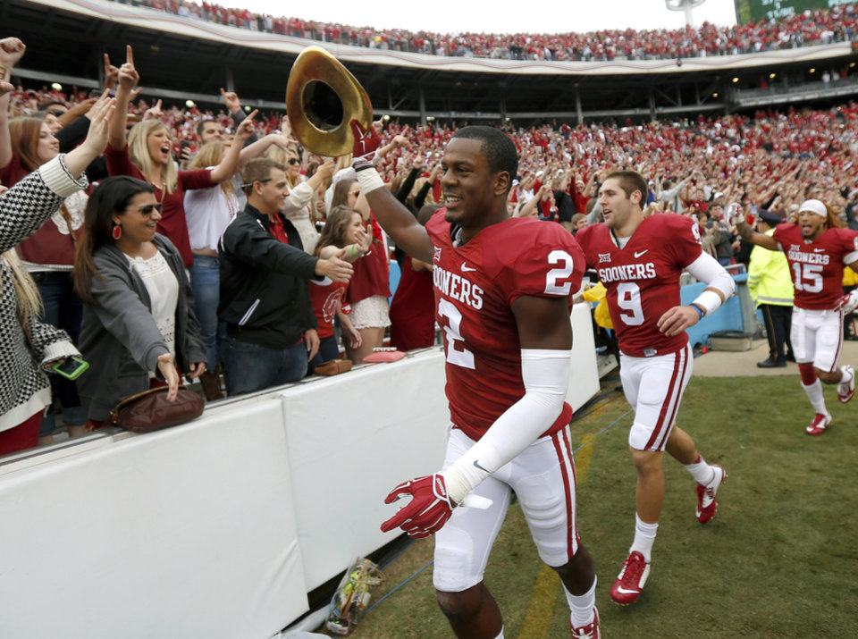 Photo - Oklahoma's Julian Wilson (2), Trevor Knight (9), and Zack Sanchez (15) celebrate after the Red River Showdown college football game between the University of Oklahoma Sooners (OU) and the University of Texas Longhorns (UT) at the Cotton Bowl in Dallas on Saturday, Oct. 11, 2014. 