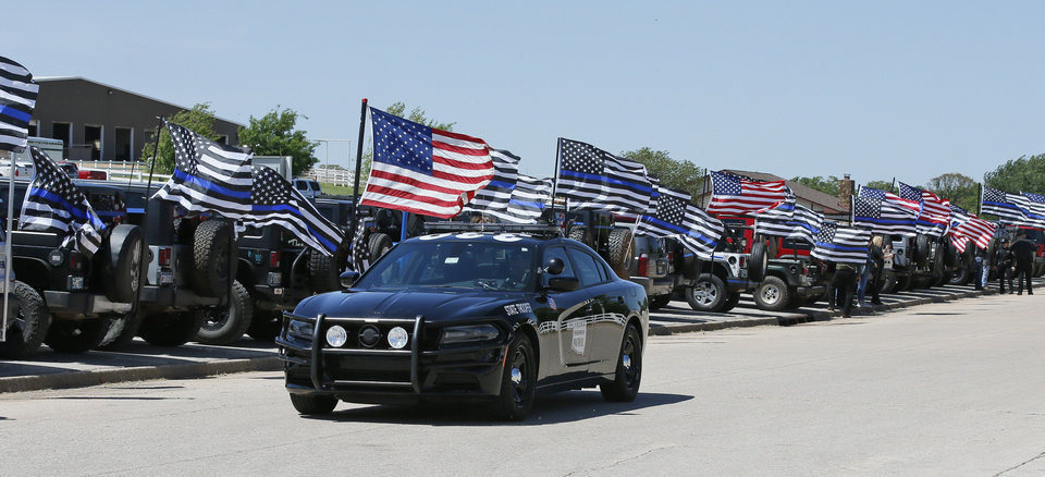 Photo - An Oklahoma Highway Patrol car drives past a line of flags on the road to the funeral of Logan County Deputy David Wave, in Guthrie, Okla., Monday, April 24, 2017. Wade was shot and killed while serving an eviction notice near Mulhall, Okla,. April 18, 2017. (AP Photo/Sue Ogrocki)