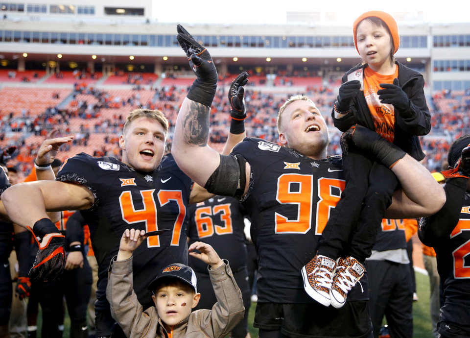 Photo - Carson Kropp (47) and Brendon Evers (98) celebrate with children from the Coaches vs. Cancer program followig the college football game between the Oklahoma State University Cowboys and the TCU Horned Frogs at Boone Pickens Stadium in Stillwater, Okla.,  Saturday, Nov. 2, 2019. [Sarah Phipps/The Oklahoman]