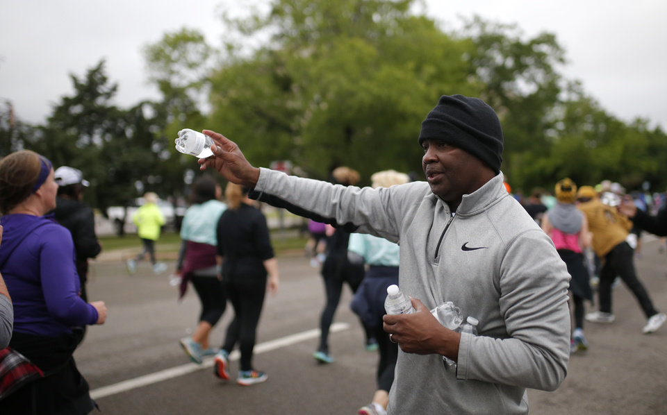 Photo - Melvin Gaines with Alpha Phi Alpha hands out water at the state capitol during the 2017 Oklahoma City Memorial Marathon Sunday, April 30, 2017.  Photo by Sarah Phipps, The Oklahoman