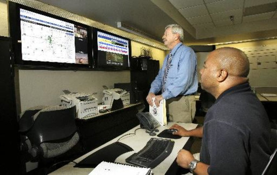 Photo - Michael Murphy, standing, director of the Metropolitan Medical Response System, and Michael Curtis, seated, coordinator of the Oklahoma City Medical Emergency Response Center, examine a weather screen at the response center April 23, 2009.  Paul B. Southerland - The Oklahoman