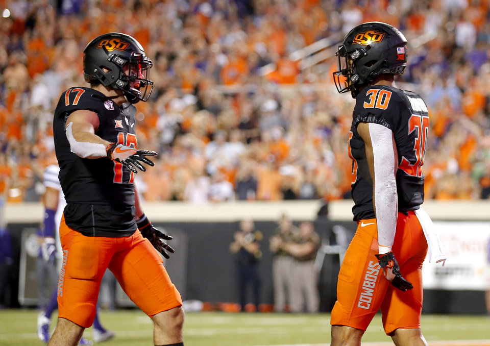 Photo - Oklahoma State's Chuba Hubbard (30) celebrates his touchdown with Oklahoma State's Dillon Stoner (17) in the third quarter during the college football game between the Oklahoma State Cowboys and the Kansas State Wildcats at Boone Pickens Stadium in Stillwater, Okla., Saturday, Sept. 28, 2019. [Sarah Phipps/The Oklahoman]
