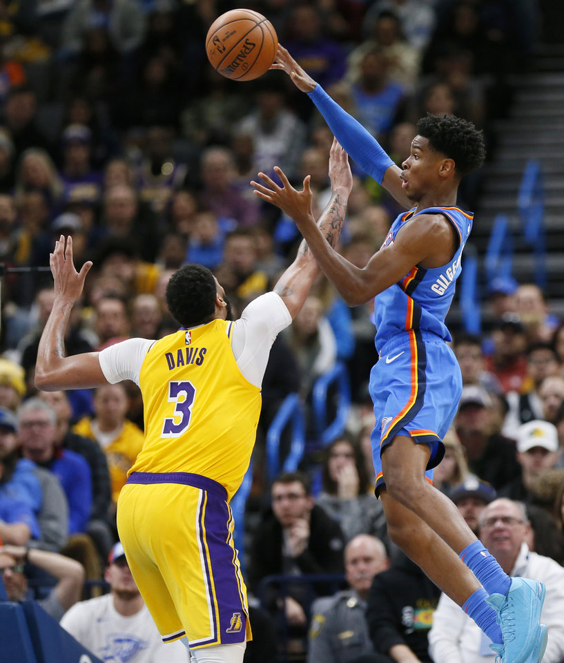 Photo - Oklahoma City's Shai Gilgeous-Alexander (2) passes over Los Angeles' Anthony Davis (3) in the third quarter during an NBA basketball game between the Oklahoma City Thunder and the Los Angeles Lakers at Chesapeake Energy Arena in Oklahoma City, Friday, Nov. 22, 2019. The Lakers won 130-127. [Nate Billings/The Oklahoman]