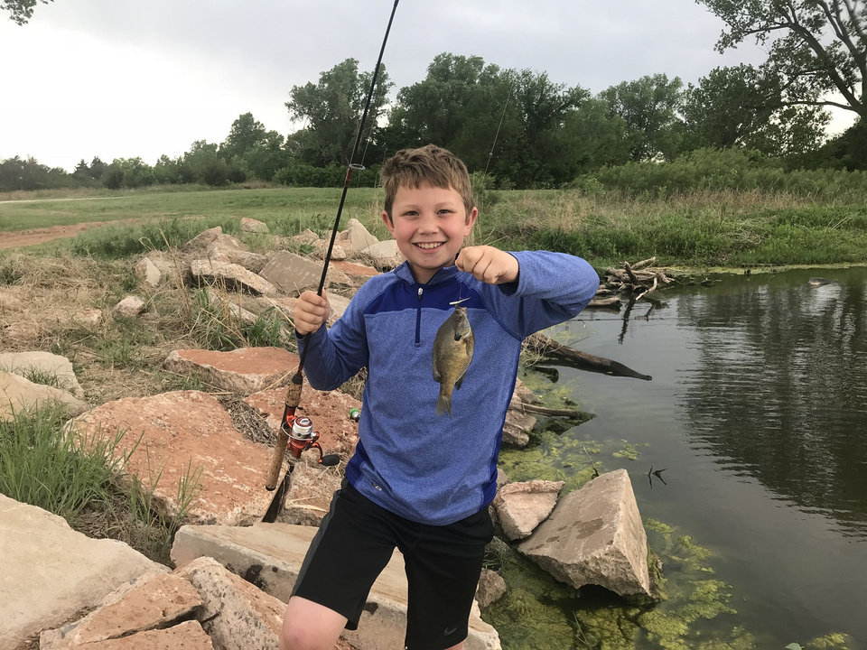Photo -  Rylan Kuklinski, 9, from Norman holds a bluegill that he caught at Elmer Lake near Kingfisher. [PHOTO PROVIDED]