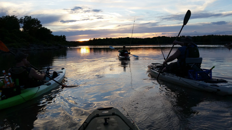 Photo -  Four anglers in kayaks take off at sunset on Oologah Lake. [PHOTO BY BRENT WILSON]