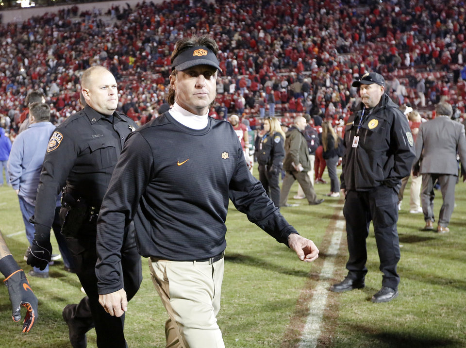 Photo - Oklahoma State head coach Mike Gundy leaves the field following a Bedlam college football game between the University of Oklahoma Sooners (OU) and the Oklahoma State University Cowboys (OSU) at Gaylord Family-Oklahoma Memorial Stadium in Norman, Okla., Nov. 10, 2018.  Photo by Sarah Phipps, The Oklahoman