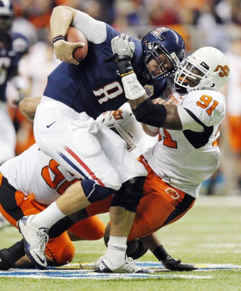 Photo -  OSU's Ugo Chinasa (91) sacks Arizona quarterback Nick Foles (8) with the help of OSU's Jamie Blatnick (50) in the first quarter during the Valero Alamo Bowl college football game between the Oklahoma State University Cowboys (OSU) and the University of Arizona Wildcats at the Alamodome in San Antonio, Texas, Wednesday, December 29, 2010. Photo by Nate Billings, The Oklahoman ORG XMIT: KOD