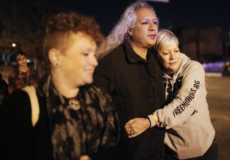 Photo - Sara Cunningham hugs Sharon Queen as they walk during a Transgender Day of Remembrance walk and vigil in Oklahoma City, Tuesday, Nov. 20, 2018. Photo by Sarah Phipps, The Oklahoman