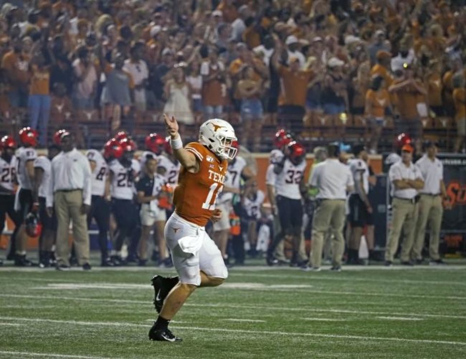 Photo -  Sam Ehlinger celebrates a touchdown during Texas' 36-30 win against Oklahoma State on Sept. 21 in Austin. [AP Photo/Michael Thomas}
