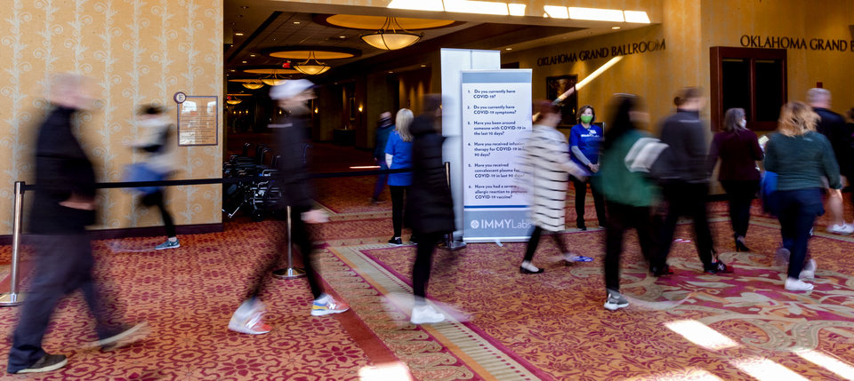 Photo - People file in for the Covid-19 vaccination pod at the Embassy Suites by Hilton Norman Hotel & Conference Center in Norman, Okla. on Monday, Feb. 22, 2021.  [Chris Landsberger/The Oklahoman]