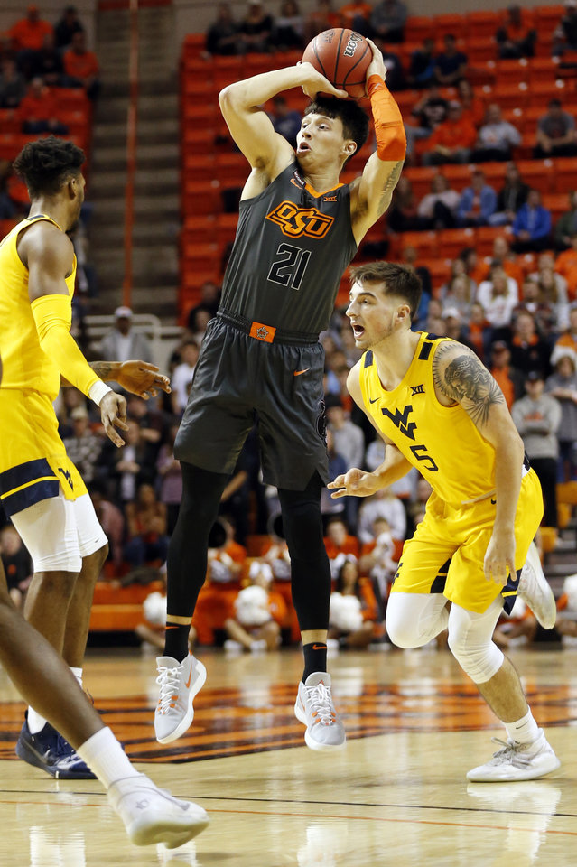 Photo - Oklahoma State's Lindy Waters III (21) shoots next to West Virginia's Jordan McCabe (5) in the first half during a men's college basketball game between the Oklahoma State Cowboys and West Virginia Mountaineers at Gallagher-Iba Arena in Stillwater, Okla., Monday, Jan. 6, 2020. [Nate Billings/The Oklahoman]