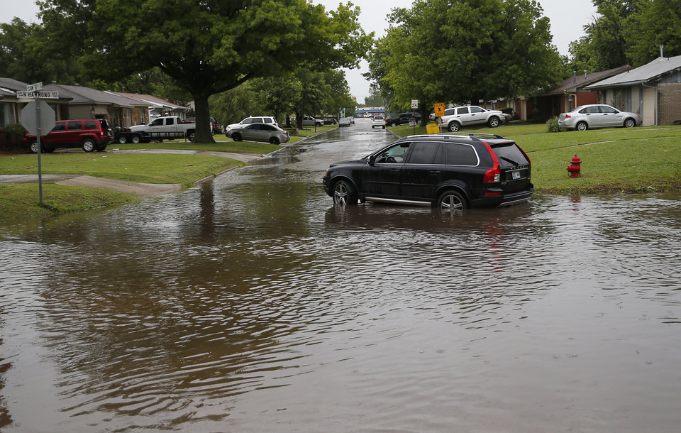 Photo - A car is abandoned in high waters at NW 34th and Hammond in Warr Acres, Okla., after severe storms moved through the metro area, Saturday, May 18, 2019 Photo by Sarah Phipps, The Oklahoman