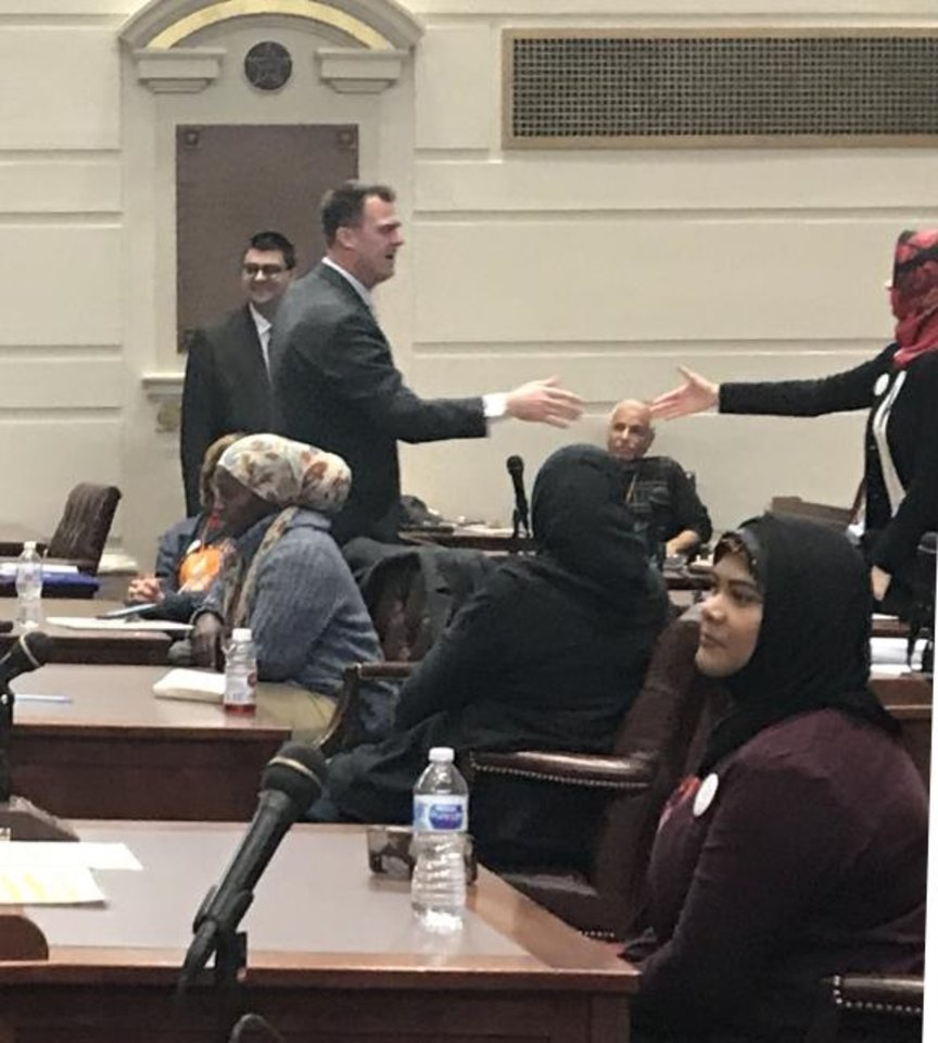 Photo -  Gov. Kevin Stitt shakes hands with Kuaybe Basturk, a Dialogue Institute board member attending Muslim Day at the Capitol activities in the Senate Chamber on Monday at the state Capitol. [Carla Hinton/The Oklahoman]