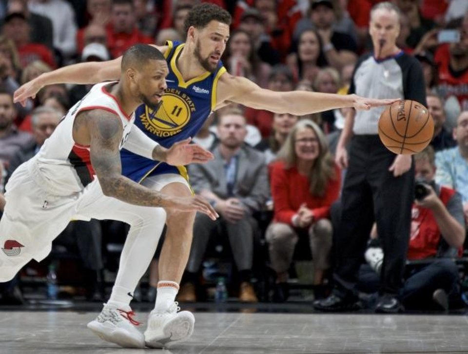 Photo -  Golden State's Klay Thompson, right, and Portland's Damian Lillard battle for a loose ball during the Western Conference Finals. Lillard made the All-NBA team on Thursday but Thompson did not, which makes a difference in the kinds of contracts they can sign. [AP Photo/Craig Mitchelldyer]