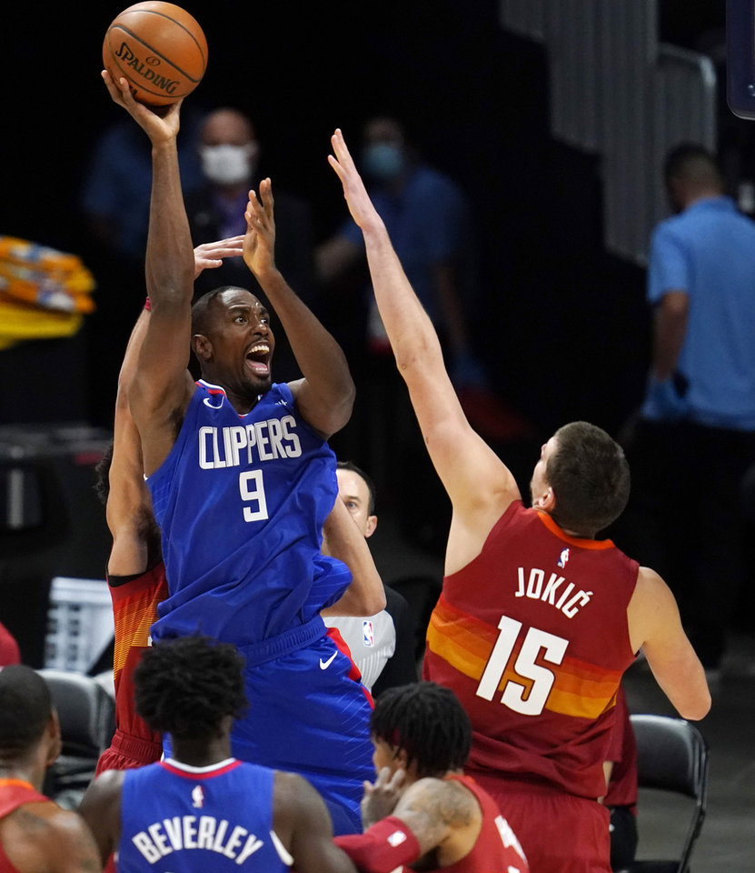 Photo - Los Angeles Clippers forward Serge Ibaka shoots over Denver Nuggets center Nikola Jokic during the first half of an NBA basketball game Friday, Dec. 25, 2020, in Denver. (AP Photo/David Zalubowski)