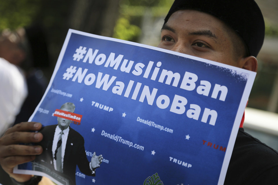 Photo - A Muslim protesters holds a placard while demonstrating against U.S. President Trump's immigration ban outside the U.S. Embassy in Kuala Lumpur, Malaysia, on Friday, Feb. 3, 2017. Trump's order temporarily halted the entire U.S. refugee program and banned all entries from seven Muslim-majority nations for 90 days. (AP Photo/Vincent Thian)