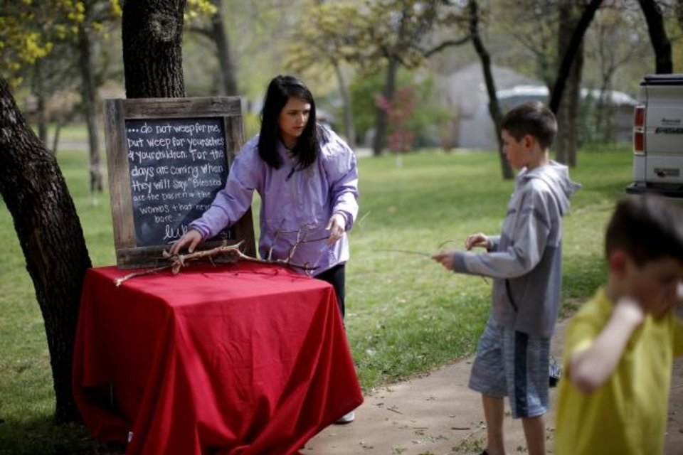 Photo -  Stephanie Stovall and her son Blake, 10, gather sticks while assembling a scene for a drive-thru Stations of the Cross. [Bryan Terry/The Oklahoman]