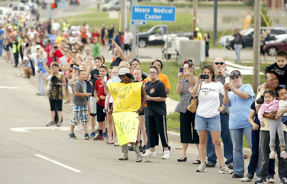 Photo - A crowd lines SW 19 in Moore on Sunday as President Barack Obama arrives. Along the route, people waved small American flags and took photographs.